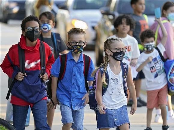 Các em nhỏ đeo khẩu trang phòng dịch Covid-19 khi ngày đầu tiên trở lại trường học sau thời gian dài giãn cách, tại Riverview, bang Florida (Mỹ) ngày 10-8-2021. Ảnh minh họa: AP/TTXVN