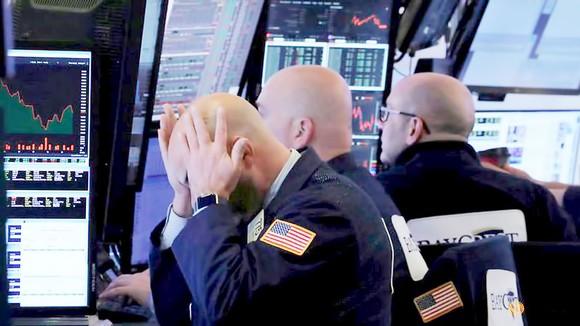 Nhân viên giao dịch tại Sàn chứng khoán New York theo dõi chỉ số chứng khoán sụt giảm mạnh