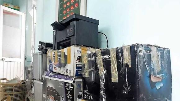 Tang vật với máy in, thùng đựng bằng giả của một tổ chức làm các văn bằng, chứng chỉ giả quy mô cực lớn vừa được Công an TPHCM phát hiện. Ảnh: THANH HÙNG