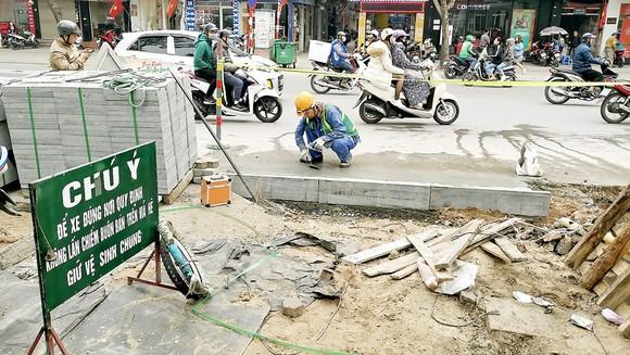 Thi công lát đá vỉa hè trên phố Thái Hà, Hà Nội. Ảnh: VIẾT CHUNG