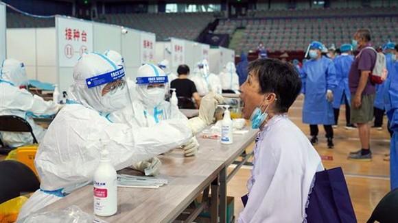 Nhân viên y tế lấy mẫu xét nghiệm Covid-19 cho người dân Trung Quốc. Ảnh: TTXVN