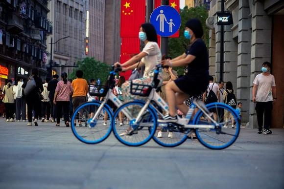 Phụ nữ đạp xe trên đường phố ở thành phố Thượng Hải, Trung Quốc, 10-5-2021. Ảnh: REUTERS