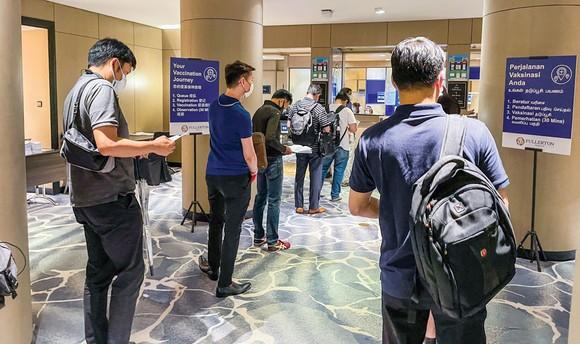 Người dân Singapore xếp hàng làm thủ tục tiêm vaccine Covid-19.
