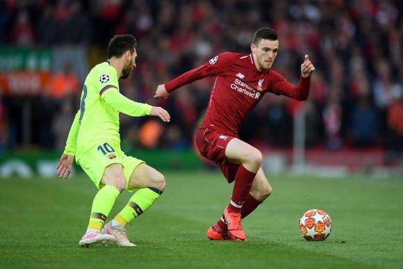 Andy Robertson (phải) cố gắng đi bóng qua Lionel Messi