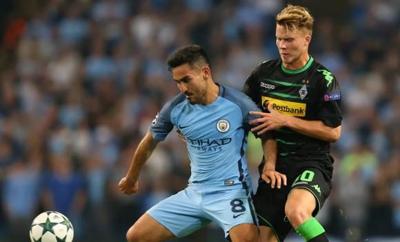 Ilkay Gundogan (trái, Manchester City) tranh bóng với Nico Elved (Borussia Mönchengladbach)