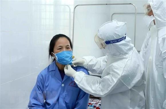 Bác sỹ Đội cơ động Bệnh viện Bạch Mai (Hà Nội) thăm khám cho bệnh nhân tại Trung tâm y tế huyện Bình Xuyên, Vĩnh Phúc. (Ảnh: Hoàng Hùng/TTXVN)