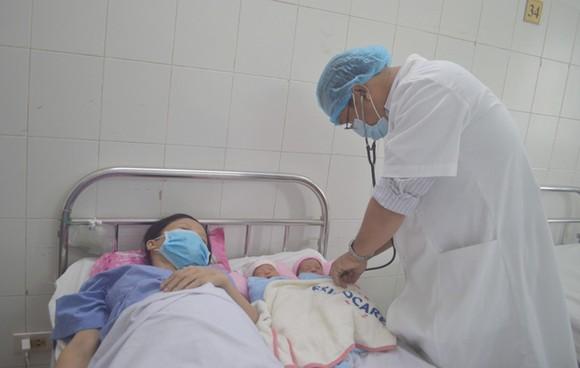 Bác sĩ chăm sóc cho sản phụ và 2 bé