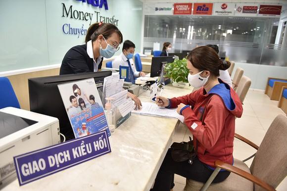 Nhận kiều hối tại một ngân hàng trên đường Nguyễn Thị Minh Khai, Q.3, TP.HCM - Ảnh: NGỌC PHƯỢNG