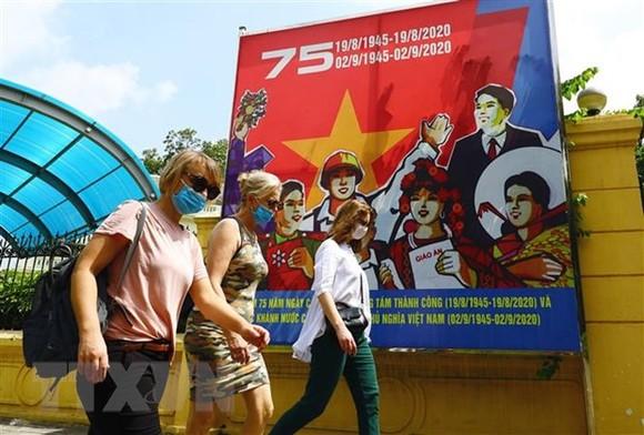 Du khách quốc tế đeo khẩu trang, dạo bộ trên phố Điện Biên Phủ. (Ảnh: Lâm Khánh/TTXVN)