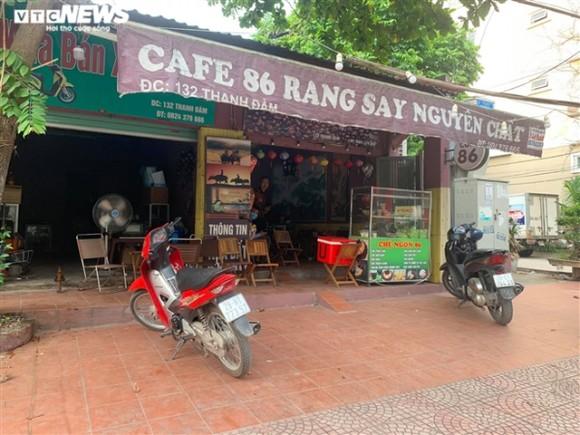 Một quán cà phê vắng bóng khách, chỉ có nhân viên phục vụ.