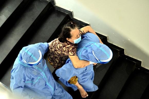Một bệnh nhân F0 trở nặng khó thở được các bác sĩ và điều dưỡng cõng từ lầu 2 xuống phòng cấp cứu tầng trệt tại Bệnh viện dã chiến Chi Lăng, quận 4, TP.HCM - Ảnh: TỰ TRUNG