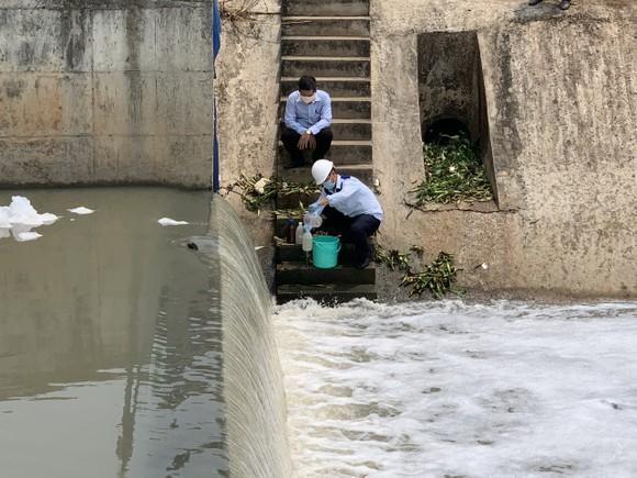 Lực lượng chức năng lấy mẫu nước xét nghiệm