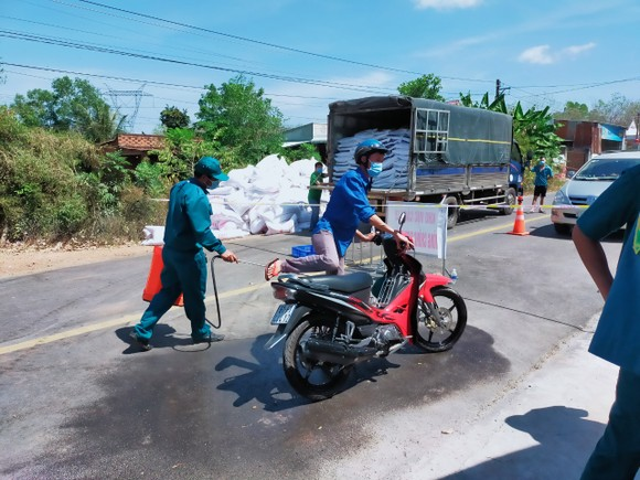 Lực lượng chức năng xã An Bình, huyện Phú Giáo phun thuốc khử khuẩn phương tiện ở ấp Cà Na. Ảnh chụp tháng 2-2021