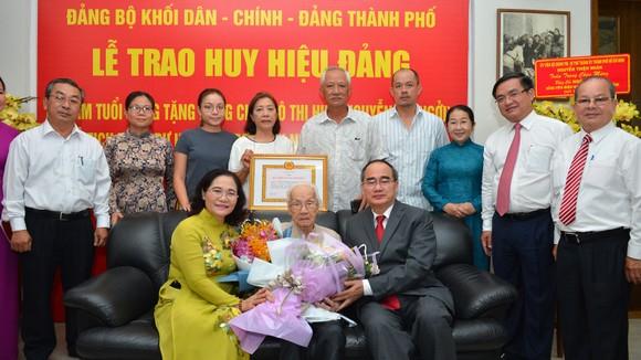 Bí thư Thành ủy TPHCM Nguyễn Thiện Nhân cùng các đồng chí lãnh đạo TP, gia đình chúc mừng đồng chí Ngô Thị Huệ đón nhận huy hiệu 85 năm tuổi đảng. Ảnh: VIỆT DŨNG