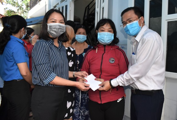 Ông Cao Thanh Bình, Chánh Văn phòng Đoàn ĐBQH và HĐND TPHCM và bà Nguyễn Thị Hiếu Hạnh, Bí thư Đảng ủy phường Tăng Nhơn Phú B tặng quà các hộ dân bị ảnh hưởng do cơn mưa chiều ngày 21-5