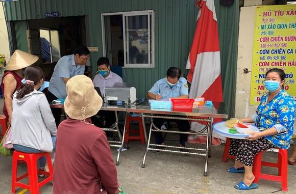 Người dân quận 11 thực hiện khai báo y tế khi đi chợ