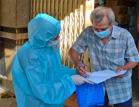 Cán bộ phường ở quận 11, TPHCM đến tận nhà chi tiền hỗ trợ người dân gặp khó khăn do ảnh hưởng dịch Covid-19