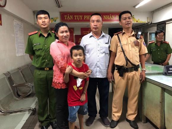Người mẹ vui mừng khi nhận được con trai 7 tuổi từ lực lượng CSGT. Ảnh: CHÍ THẠCH