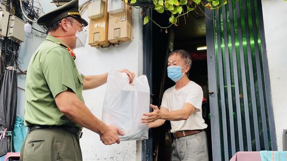 Thiếu tướng Cao Đăng Hưng, Phó Giám đốc Công an TPHCM trao quà tặng cho bà con ở khu Mả Lạng