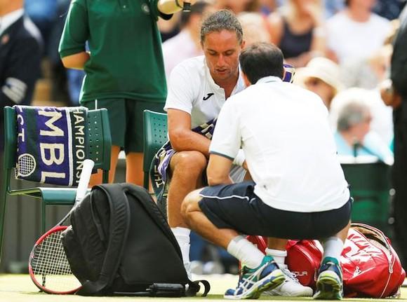 Alexander Dolgopolov đang nhờ nhân viên y tế chăm sóc chấn thương