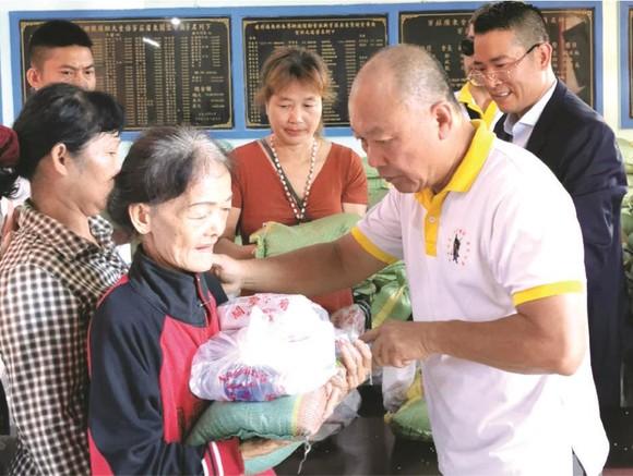 鄭成龍理事長向窮人派發禮物。