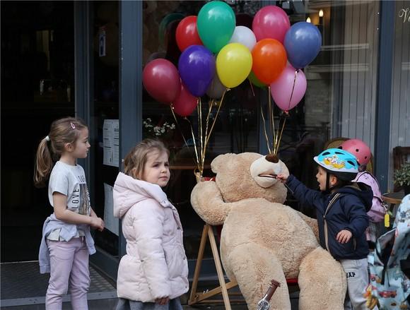 孩子們被法國巴黎街頭一家餐館外的玩具熊吸引。