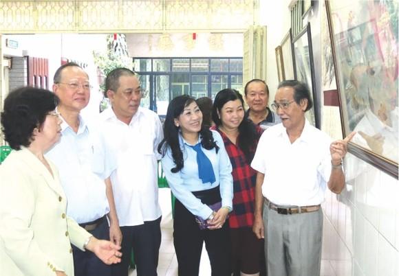 李松年書法家(右一)向參與者介紹陳列的書畫。