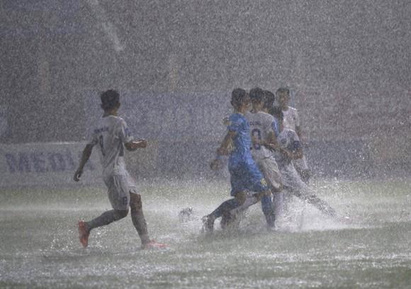 Cơn mưa to trên sân Nha Trang đã làm cho trận đấu tạm dừng từ phút 24. Ảnh: Duy Phạm