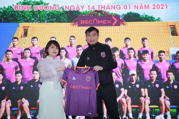 HLV Phan Thanh Hùng cùng đại diện nhà tài trợ giới thiệu mẫu áo thi đấu ở mùa bóng 2021. Ảnh: DŨNG PHƯƠNG