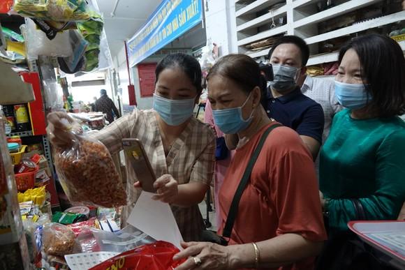 Thành viên Ban quản lý các chợ quận Hải Châu hướng dẫn người dân quét mã QR Code trên điện thoại thông minh