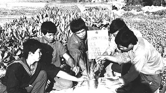 Các chiến sĩ viếng mộ đồng đội hy sinh ngày 14-3-1988 được an táng  trên đảo Sinh Tồn.  Ảnh Tư liệu