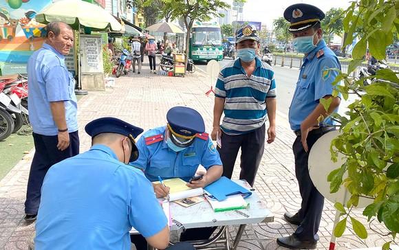 Thanh tra GTVT lập biên bản vi phạm quy định về đảm bảo trật tự an toàn giao thông trên đường Kinh Dương Vương, quận Bình Tân. Ảnh: CAO THĂNG