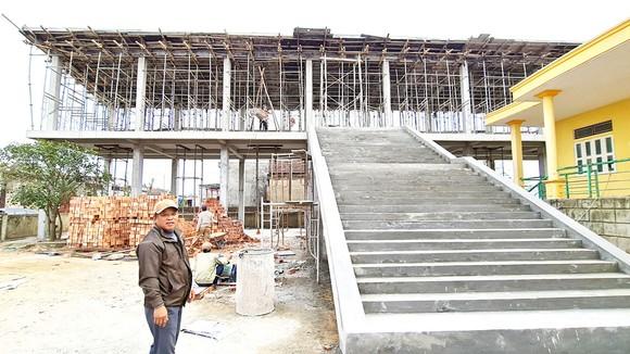 Trưởng thôn Nguyễn Trọng Trới bên căn nhà vượt lũ của thôn đang trong quá trình hoàn thiện. Ảnh: MINH PHONG