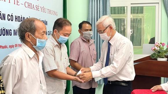 Ông Phạm Ngọc Thuận, đại diện Tổng công ty Becamex IDC trao BHYT đến bà con gặp khó khăn