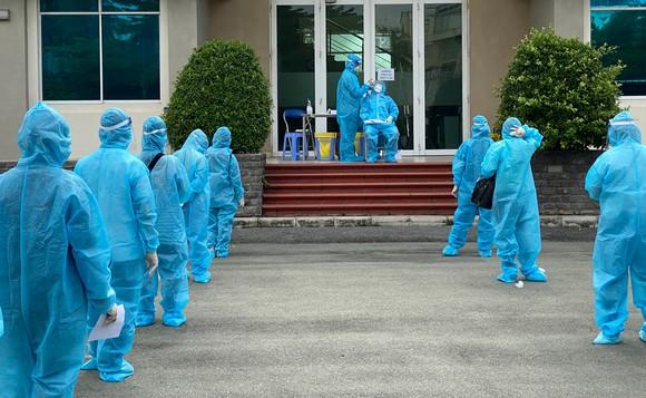 Người lao động xếp hàng chờ tầm soát Covid-19 trước khi vào sản xuất tại KCX Tân Thuận sáng 20-8. Ảnh: CAO THĂNG