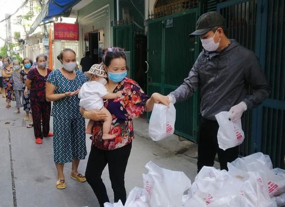 Anh Huỳnh Duy Quang Tố, Tổ phó Tổ dân phố 27, khu phố 3, phường 11 (quận Phú Nhuận, TPHCM) phát lương thực thiết yếu cho người dân có hoàn cảnh khó khăn trong tổ