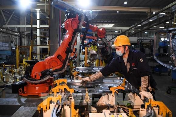 Công nhân làm việc bên trong một nhà máy ở Du Bắc, tỉnh Trùng Khánh, Trung Quốc. Ảnh: THX/TTXVN