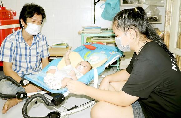 Từ ngày mẹ mất, Nguyễn Phương Quỳnh Như (quận Tân Bình) thay mẹ lo cho em mới hơn  2 tháng tuổi. Ảnh: THÁI PHƯƠNG
