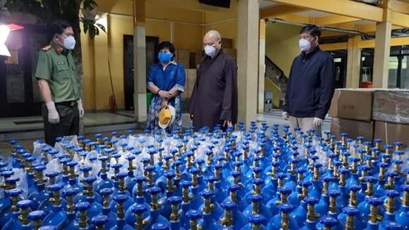 Đại tá Đinh Văn Nơi (bìa trái), Giám đốc Công an tỉnh An Giang tiếp nhận 600 bình oxy phục vụ chữa trị người mắc Covid-19