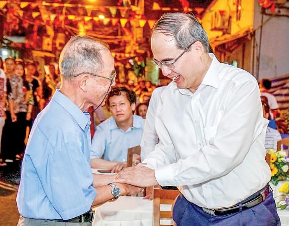Bí thư Thành ủy TPHCM Nguyễn Thiện Nhân thăm hỏi sức khỏe ông Nguyễn Xuân Thơm (thủy thủ tàu Không số), đảng viên khu phố 1, phường 12, quận 4 Ảnh: HOÀNG HÙNG