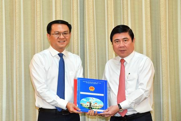 Chủ tịch UBND TPHCM Nguyễn Thành Phong trao quyết định cho đồng chí Lâm Đình Thắng. Ảnh: VIỆT DŨNG