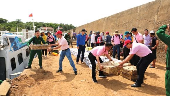 Các tình nguyện viên CPV cùng các chiến sĩ vận chuyển gà con giống ra đảo