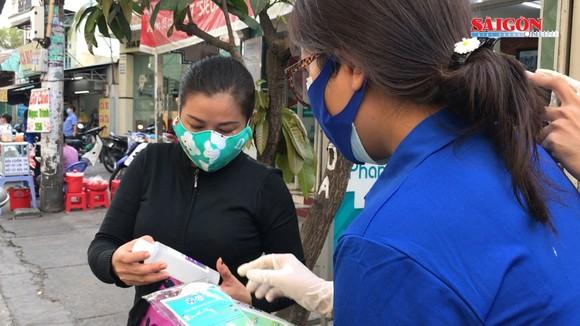 Tình nguyện viên tặng khẩu trang, nước rửa tay cho người bán hàng rong