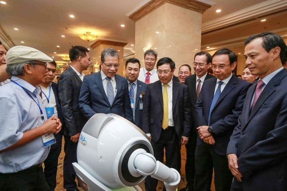 Deputy Prime Minister, Pham Binh Minh; and Secretary of the HCMC Party Committee, Nguyen Van Nen see exhibits at a display on high-tech products in the meeting. (Photo: SGGP)