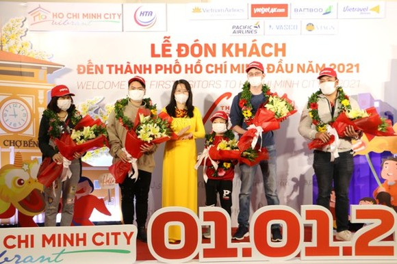 Director of the municipal Department of Tourism, Nguyen Thi Anh Hoa (C) offers flowers to first visitors to HCMC. (Photo: SGGP)