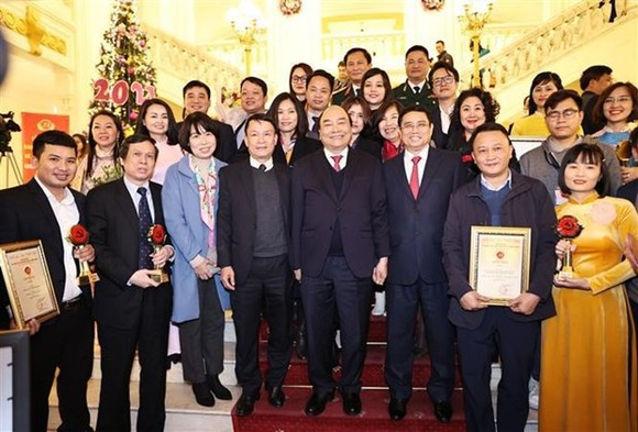 Prime Minister Nguyen Xuan Phuc (C) and Vietnam News Agency leaders pose for a photo with VNA journalists who win prizes of  fifth National Press Awards on Party building (Photo: VNA)