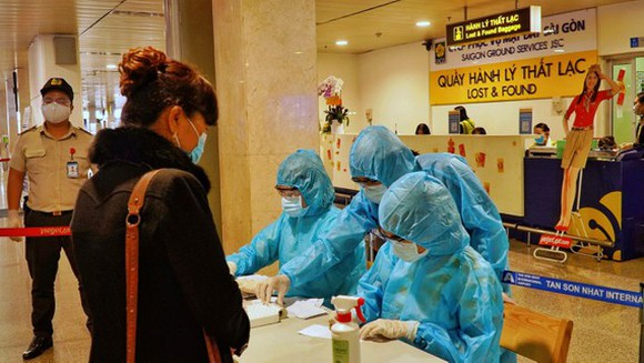 HCMC's authorities conduct random Covid-19 tests on passengers arriving at Tan Son Nhat International Airport. (Photo: SGGP)