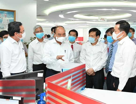 President Nguyen Xuan Phuc (C) and Secretary of the Party Committee of HCMC Nguyen Van Nen (L) visit the SGGP Newspaper. (Photo: SGGP)