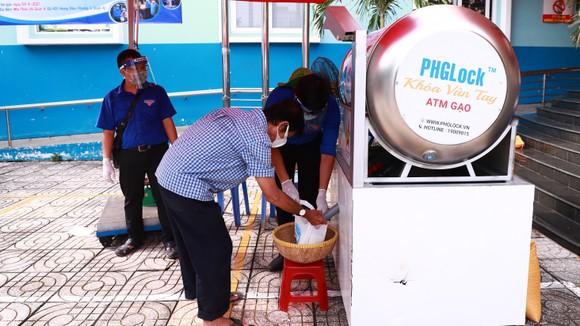 Người dân khó khăn nhận gạo từ máy ATM gạo