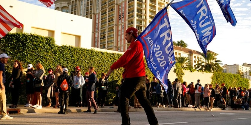Josh Platillero, of Knoxville, Tenn. skates with flags in support of President Trump as people wait for the doors to open outside of the Turning Point USA Student Action Summit, Tuesday, Dec. 22, 2020, in West Palm Beach, Fla. (AP Photo/Lynne Sladky)